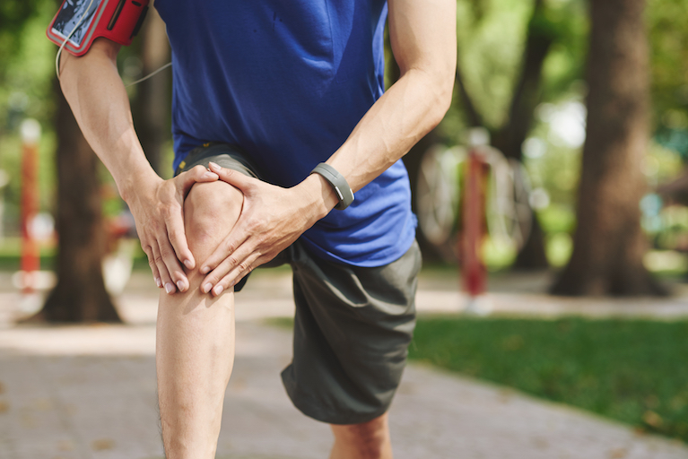 Cropped image of man rubbing his knee after jogging